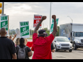 "Strikers shown from behind, waving at cars, fists in air, signs read ""UAW On Strike"""