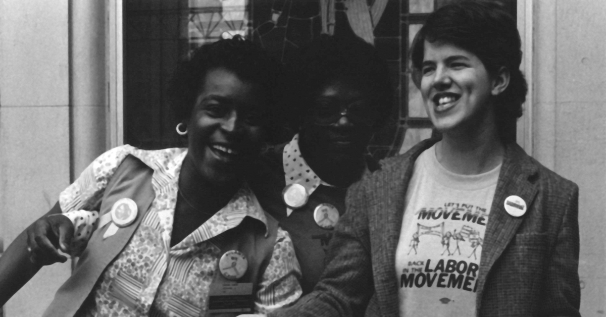 Multiracial group of activists standing next to each other and laughing.