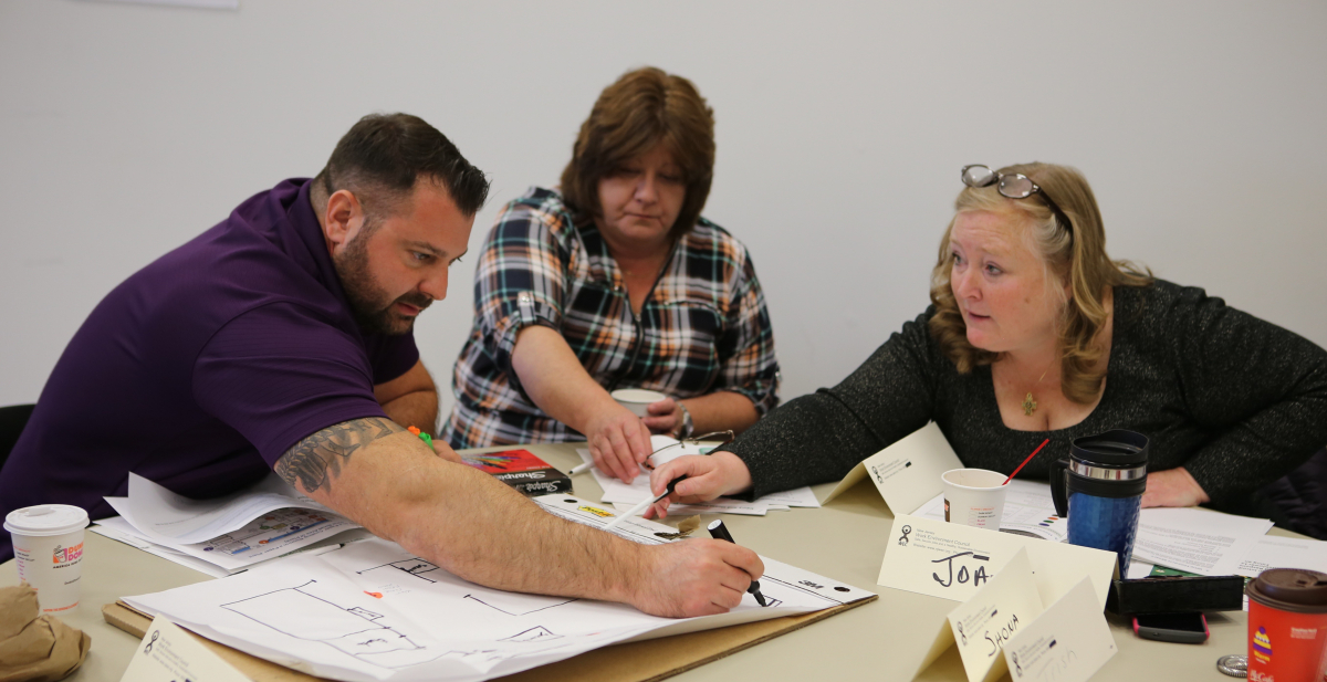 Three workers seated around a table collaborate to draw a hazard map