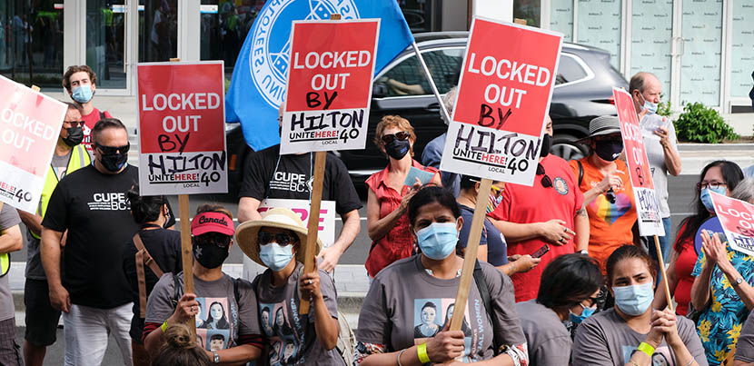 Hilton Vancouver Metrotown workers with signs fighting for their recall rights.