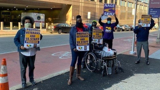 "four protesters hold signs: ""PROTECT VETERANS AND VA STAFF #VACOVID"" AND ""NAGE SEIU"""