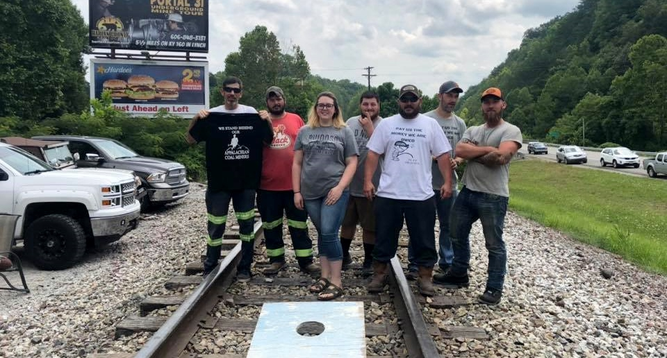 "Five people stand on railroad tracks, with a cornhole game at their feet. Some wear ""pay us what we are owed"" shirts."