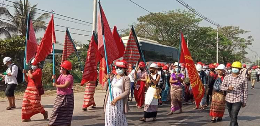 Women marching in the streets with red flags in Burma.