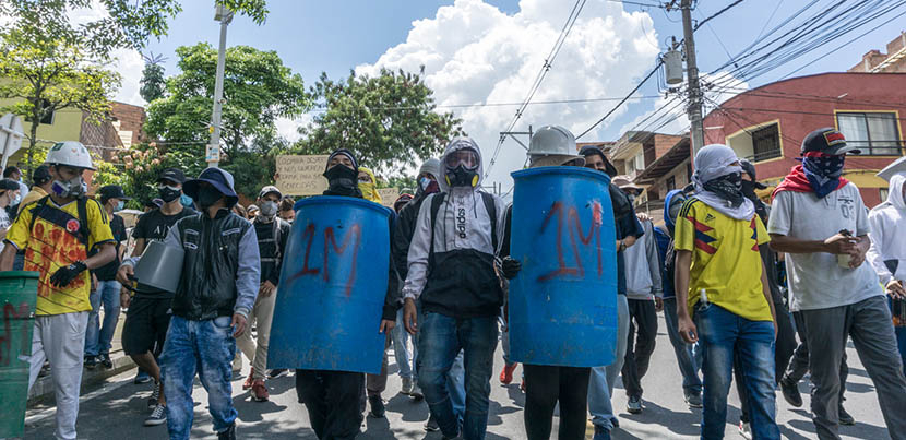Row of protesters blockading the street in Colombia, two of whom are wielding blue shields of some kind.