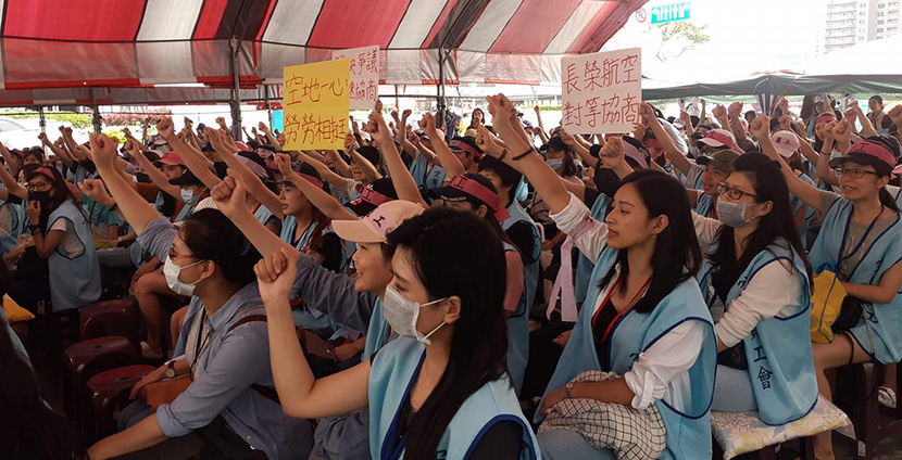 Taiwanese flight staff assembled in protest with arms raised.
