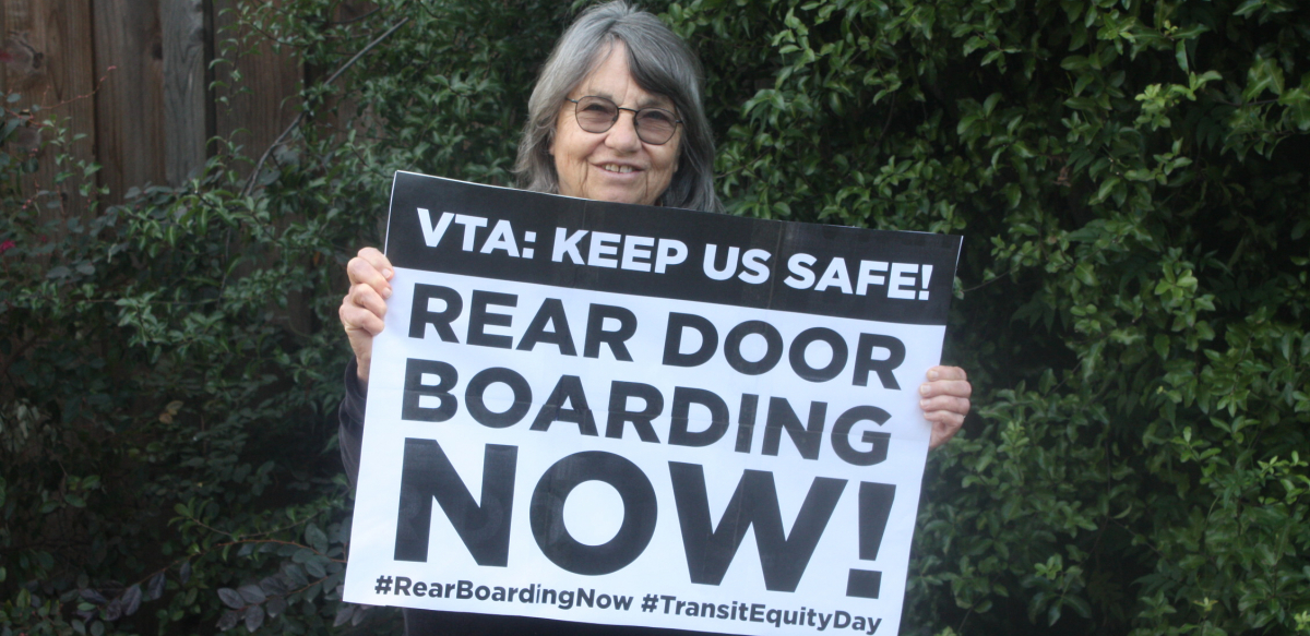 "Woman holds sign reading ""VTA: Keep Us Safe! Rear Door Boarding Now! #RearBoardingNow #TransitEquityDay"""