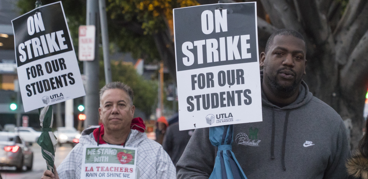 "A white man and a Black man hold signs: ""On Strike for Our Students; UTLA"""