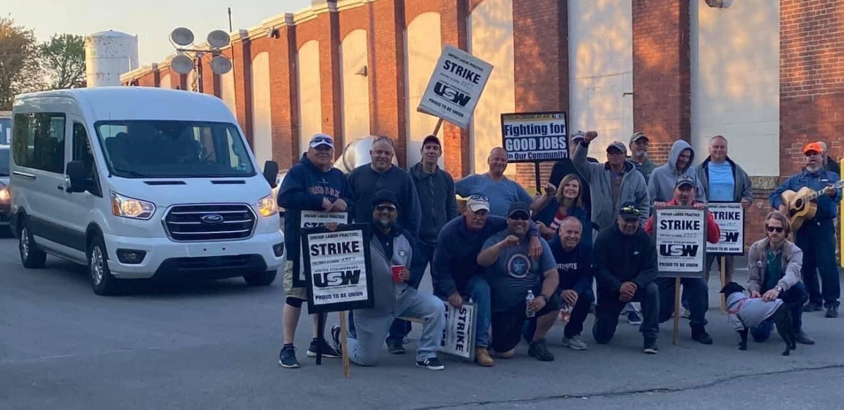 A group of striking steelworkers pose for a photo in a driveway, while a van carrying replacement workers waits behind them.