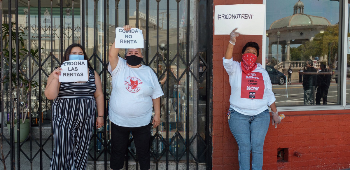 """Three women hold signs saying """"Food Not Rent"""" and """"Cancel Rent"""" in English and Spanish."""