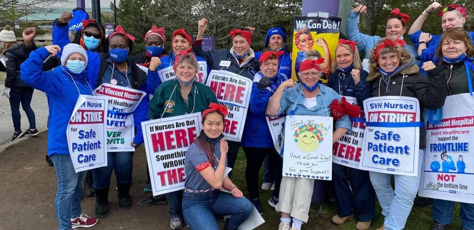 Nurses stand together holding picket signs and wearing red bandanas on their heads, a la Rosie the Riveter.
