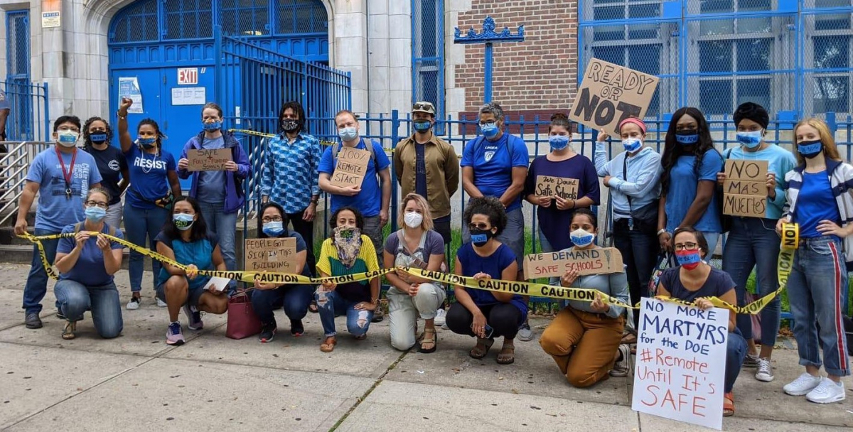 """21 adults in masks outside a school. Together they hold """"CAUTION"""" tape. Handmade signs say """"100% remote start,"""" """"no mas muertes,"""" """"ready or not,"""" """"we demand safe schools,"""" """"no more martyrs for the DOE #Remote until it's safe"""" and """"people got sick in this buidling."""""""