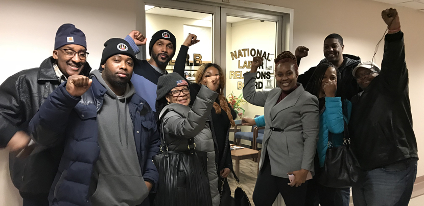 Nine Black film industry parking attendants in coats, smiling with fists up, indoors, in front of an NLRB office in New York City.