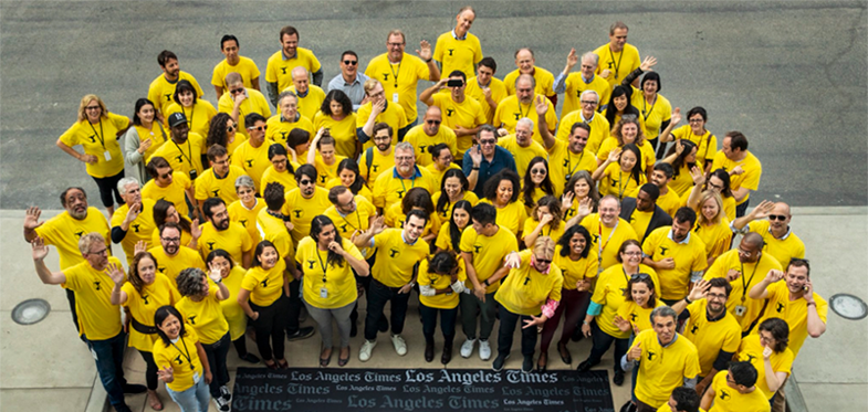 L.A. Times employees gather as NewsGuild members wearing bright yellow shirts around a plaque that says LA Times.