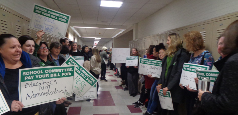 Brookline paraeducators with signs lining hallway of school.
