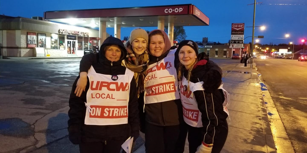 """Four smiling women wearing """"UFCW Local ON STRIKE"""" signs stand in front of a Co-op gas station, arms around each other's shoulders"""