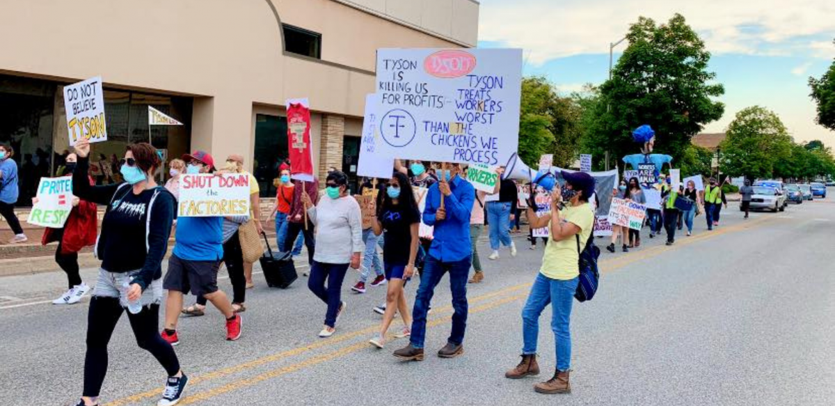"Masked people march with signs: ""Tyson Is Killing Us for Profits. Tyson Treats the Workers Worst than the Chickens We Process."" ""Don't Believe Tyson."" ""Shut Down the Factories."" ""Protect = Respect."""