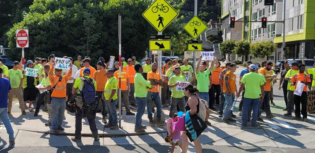 """Big crowd of carpenters in high-vis neon orange and green shirts stands on a street corner. Some hold handmade signs reading """"PAY UP AGC"""" and """"VOTE NO."""""""
