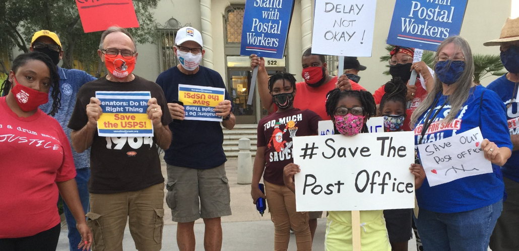 "Masked people (Black and white, men and women) holding signs. Most prominent is a handwritten sign: ""#Save the Post Office."" Preprinted signs say ""Stand with Postal Workers"" and ""Senators, do the right thing! Save USPS"""