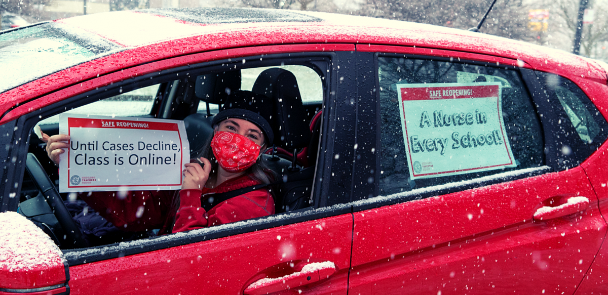 "Person in driver's seat of red car, wearing red mask, holds sign: ""Safe reopening! Until cases decline, class is online!"" Taped to back window of car is another sign: ""A nurse in every school!"" It is snowing."