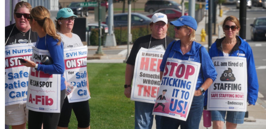 """Several nurses picket outside wearing sign. One sign says """"Stop sticking it to us!"""" with a drawing of a person in a business suit puncturing the letters with a giant syringe and needle. Another says """"G.I. am tired of [poop emoji] staffing. SAFE STAFFING NOW. -Endoscopy."""" Other signs are partially obscured but appear to say """"Don't lie, we can spot A-Fib,"""" """"If nurses are out here there's something wrong in there,"""" and """"SVH nurses on strike for safe patient care."""""""