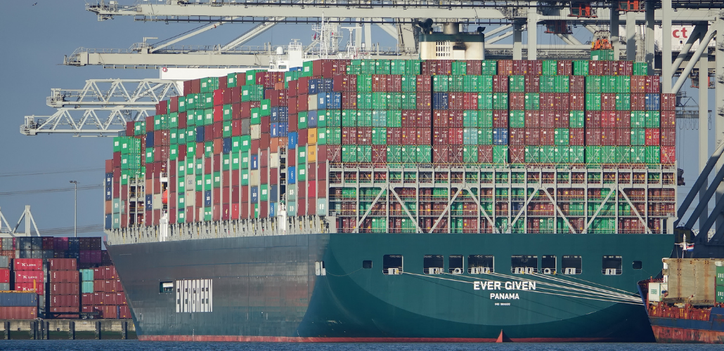 "Huge ship loaded with containers, viewed from stern which says ""Ever Given, Panama."" In the background are port cranes."