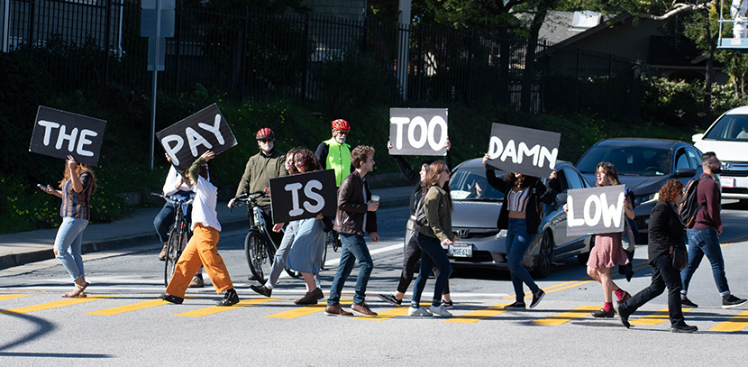 "grad students blocking traffic in the street with signs that read ""The Pay Is Too Damn Low"""