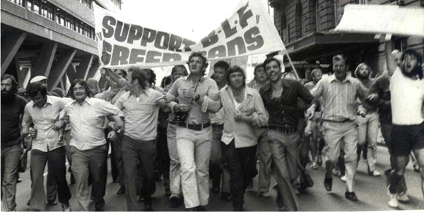 "Black and white photo of men marching with a banner: ""SUPPORT BLF GREEN BANS"""