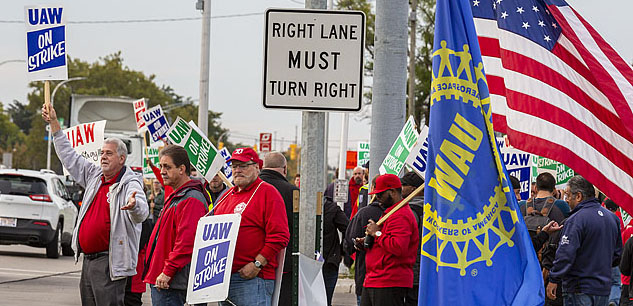 UAW strikers picketing on a street corner.