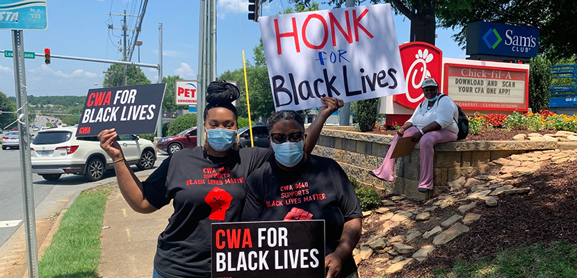Two CWA members with signs for Black lives on the pavement
