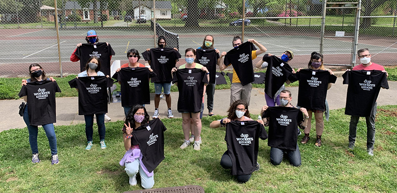 Duke University Press Workers Union posing in matching black T-shirts on grass.