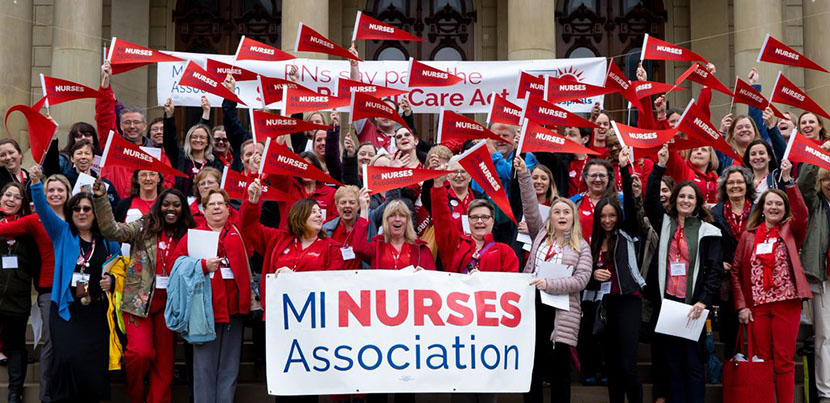 Large crowd of Michigan Nurses Association members posing in red with flags and banner on steps assembled.