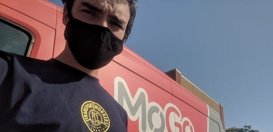 A bikeshare driver wearing a black mask stands in front of a red MoGo van.