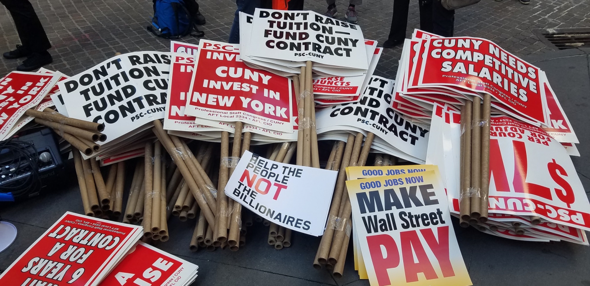 """stack of picket signs including """"don't raise tuition, fund CUNY contract,"""" """"good jobs now, make Wall Street pay,"""" """"CUNY invest in New York,"""" """"help the people, not the billionaires,"""" and """"CUNY needs competitive salaries"""""""