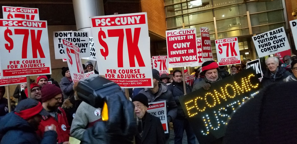 "crowd holding signs including ""PSC-CUNY $7k per course for adjuncts,"" ""invest in CUNY, invest in New York,"" and ""ECONOMIC JUSTICE"" spelled out in lights"