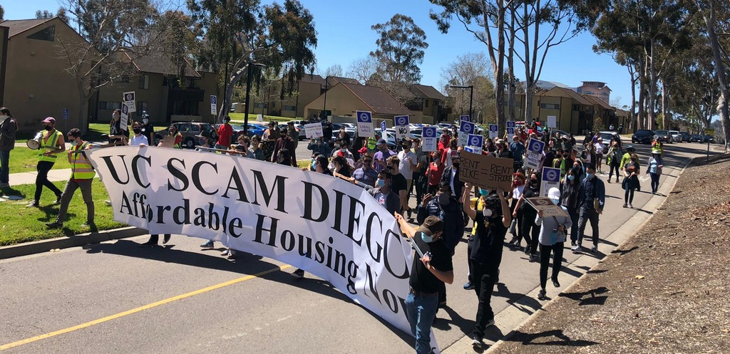 """A group marches down the street behind a banner reading """"UC Scam Diego: Affordable Housing Now."""""""
