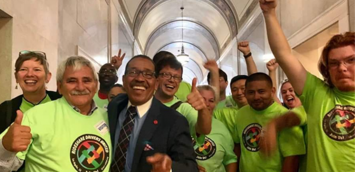 Happy people in neon yellow RDU shirts, plus a man in a suit, raise jubilant fists in a legislative hallway