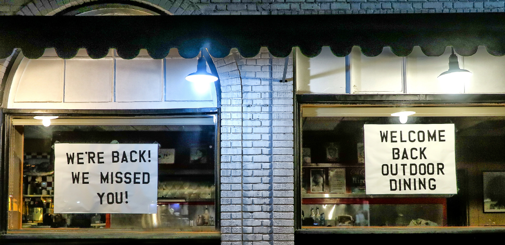 "Signs in shop windows: ""WE'RE BACK! WE MISSED YOU! WELCOME BACK OUTDOOR DINING"""