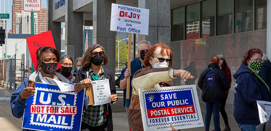 """Picketers (Black and white, men and women) marching in front of a post office. Signs say """"U.S. Mail Is Not for Sale,"""" """"Postmaster DeJoy Is Destroying Our Post Office,"""" """"Save Our Public Postal Service: Forever Essential."""" Also visible are copies of the flyer """"Dump DeJoy and His 10-Year Plan."""""""
