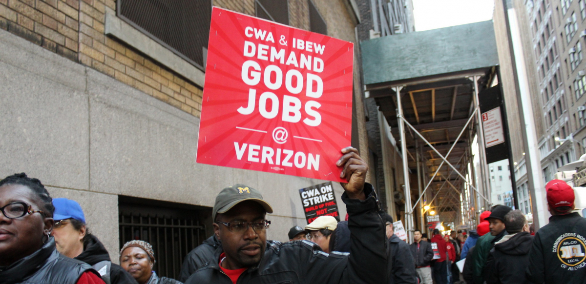 """A striking worker holds a sign saying """"CWA and IBEW Demand Good Jobs at Verizon"""" during the 2016 Verizon strike."""