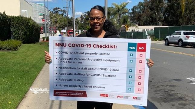 "A nurse holds a sign showing ""NNU COVID-19 Checklist: patient properly isolated, adequate PPE for nurses, notification to staff about case, adequate staffing for patient, adequate testing, nurses properly placed on leave"""