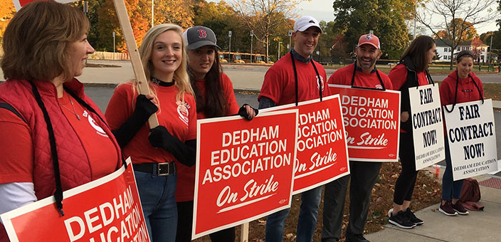 "Line of workers on picket line in red union T-shirts holding signs that say ""Dedham Education Association on Strike"" and ""Fair Contract Now"""