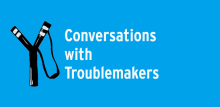 "Black slingshot on blue background with text ""Conversations with Troublemakers"""