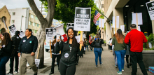 """A woman holds a bullhorn and a picket sign that says """"On Strike for a Fair Contract,"""" surrounded by dozens of picketers holding similar signs and marching in a circle on the sidewalk."""
