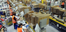 Amazon warehouse with goods on shelves and workers in orange vests working.